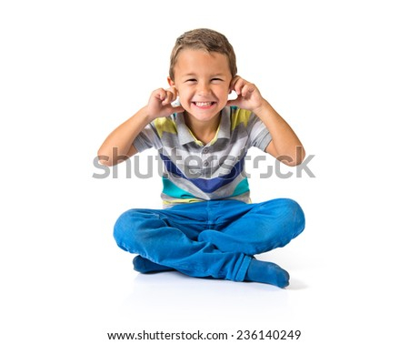 Kid covering his ears over white background - stock photo