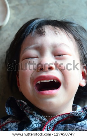 Kid crying, focus on his tear, added a bit of grain, - stock photo