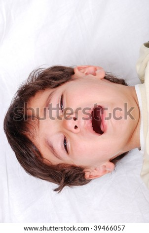 Kid crying on white sheet - stock photo