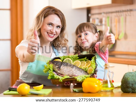 kid daughter and mother showing thumb up cooking in domestic kitchen - stock photo