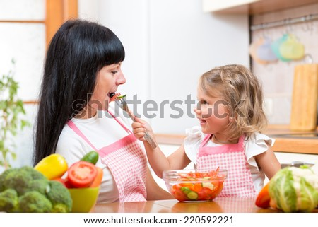 kid daughter feeding mother vegetables in kitchen - stock photo