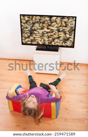 Kid does not want to watch disgusting things on the TV - stock photo