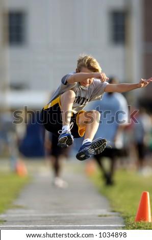kid doing long jump - stock photo