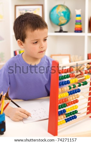 Kid doing math exercise counting with abacus - stock photo