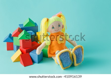 Kid doll with wooden building blocks on plain background - stock photo