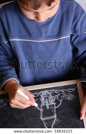 Kid drawing on a blackboard - stock photo