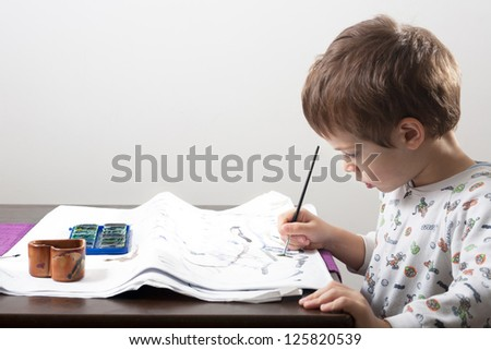 Kid drawing with water colors on table - stock photo