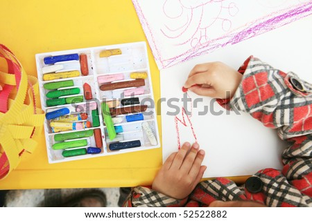 Kid  draws on a white sheet with crayons - stock photo