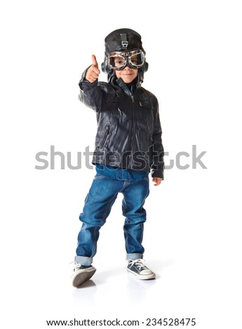Kid dressed as aviator with thumb up - stock photo
