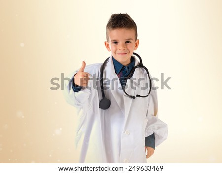 Kid dressed as doctor with thumb up - stock photo