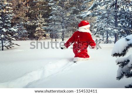 Kid dressed as Santa walks in forest - stock photo