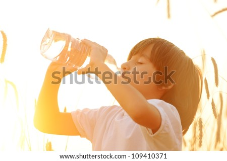 Kid drinking pure fresh water in nature - stock photo