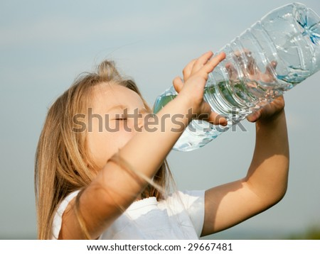 Kid drinking water from a bottle against a sky background - stock photo
