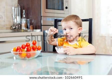 kid eating at home in kitchen