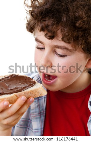Kid eating bread with nut butter isolated on white background - stock photo