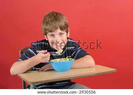 kid eating cereal at desk - stock photo