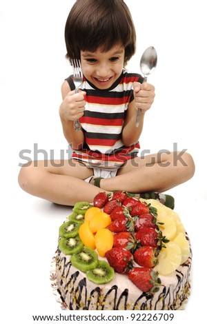 Kid eating fruit cake - stock photo