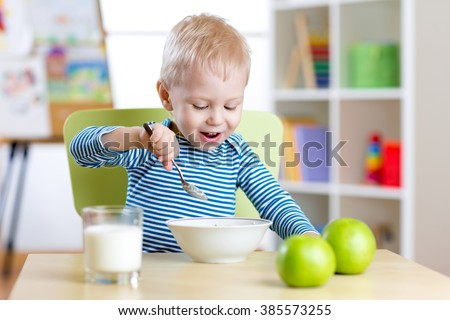 kid eating healthy food at home or kindergarten - stock photo