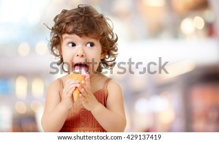 Kid eating ice cream in cafe. Funy curly child with icecream outdoor. - stock photo