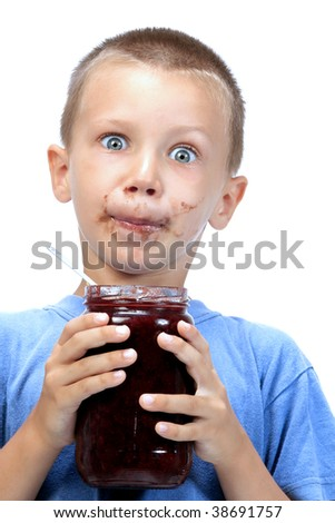 kid eating marmalade , while smearing his face with marmalade