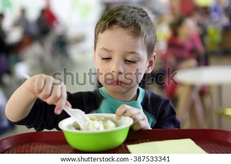 Kid eating meat dumplings in the fast food area - stock photo