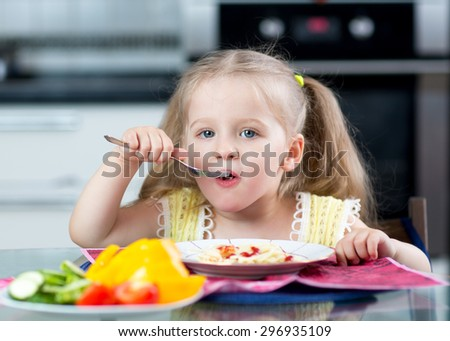 kid eating spaghetti with vegetables in nursery or at home - stock photo