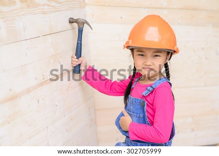 Kid engineer with carpenter work hammer on wood and make a thumb up