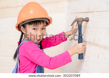 Kid engineer with carpenter work hammer on wood wall