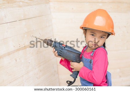 Kid engineer with carpenter work portrait holding drill on wood background