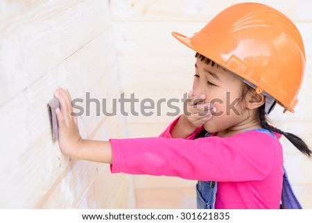 Kid engineer with carpenter work yawn with sanding on wood
