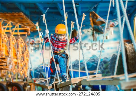 Kid enjoying a summer day and playing. Happy child having fun in adventure park, climbing ropes and laughing.  - stock photo
