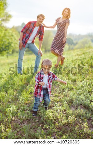 Kid enjoying holidays with his family in the park on a sunny summer day on the nature - stock photo