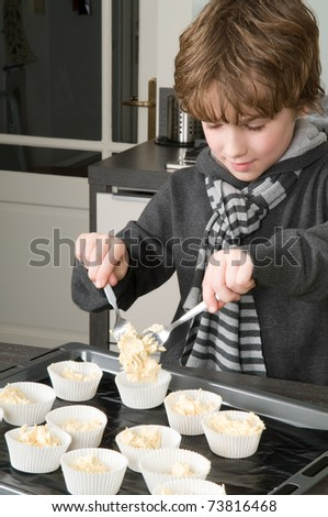 Kid filling the cakecups with the dough, for baking cakes. - stock photo