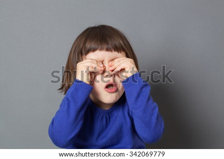 kid fun concept - cheeky preschool child playing peekaboo or hide and seek,rubbing eyes to be invisible for fun game,studio shot - stock photo