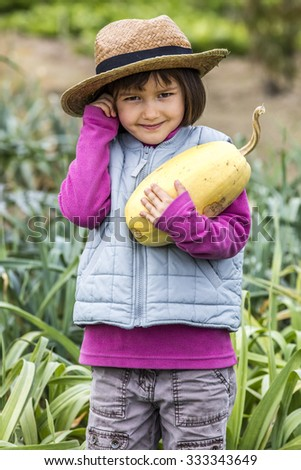 kid gardening concept - thrilled 4-year old child enjoying holding a squash with gardener straw hat on in home vegetable garden in autumn season, outdoors view - stock photo