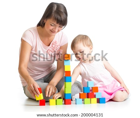 kid girl and her mom play with building blocks - stock photo