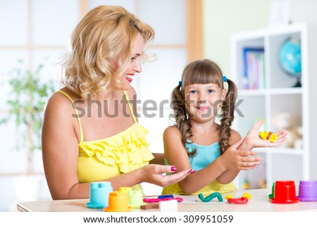 kid girl and mom play with color dough at home - stock photo