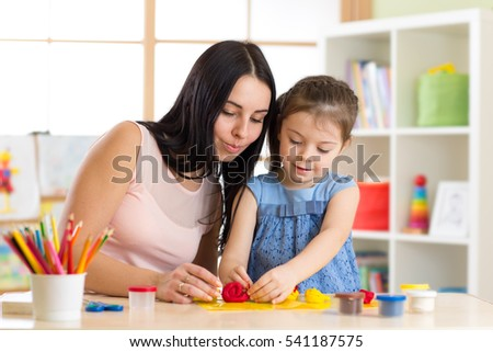 kid girl and mom play with plasticine at home
