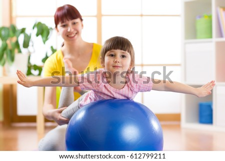 kid girl and mother doing exercises with fitness ball