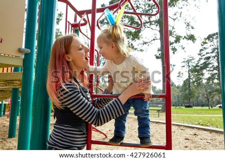 Kid girl and mother playing with playground ladder in the park - stock photo