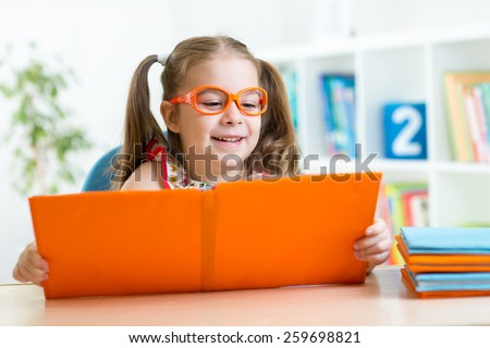 kid girl at the table with books at home interior - stock photo
