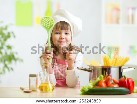 Kid girl cook makes healthy vegetables meal in the kitchen - stock photo