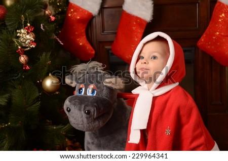 Kid girl dressed as Santa Claus  ride the  rocking-horse near christmas tree  - stock photo