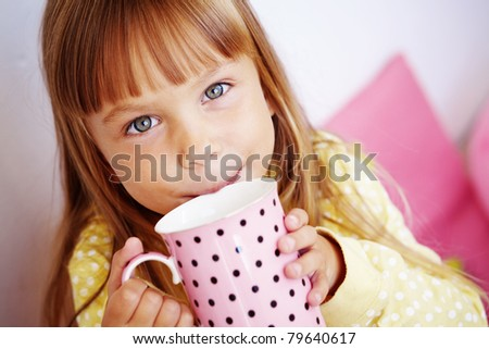 Kid girl drinking milk from cup - stock photo