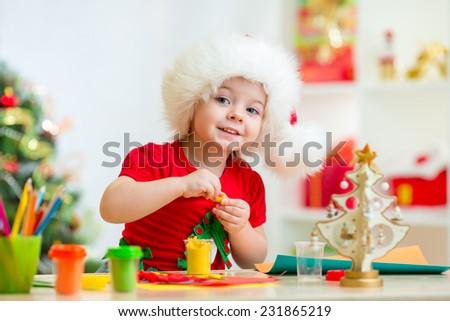 kid girl in Santa hat making Christmas tree of plasticine - stock photo