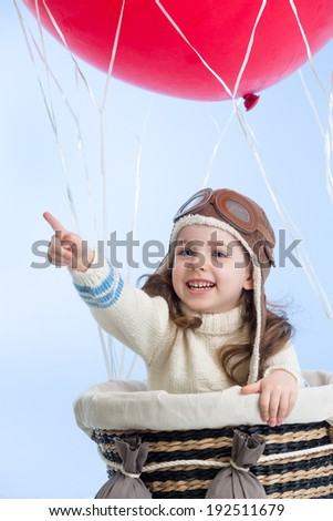 kid girl playing on hot air balloon on the sky background - stock photo
