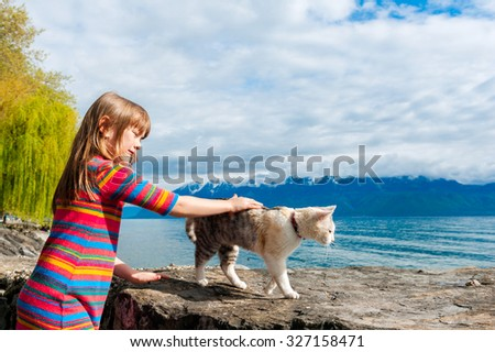 Kid girl playing with a cat outdoors, Geneva Lake, Switzerland - stock photo