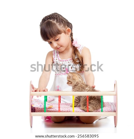 kid girl playing with a kitten and rocking him in doll crib - stock photo