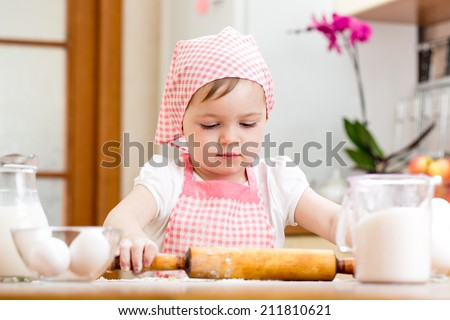 kid girl preparing dough in the kitchen at home - stock photo