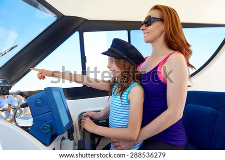 Kid girl pretending be a captain sailor cap with her mother in boat indoor - stock photo